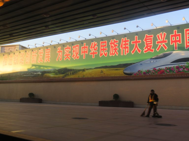 """Photo: Lukas Knoflach. Cleaning staff at a train station in Beijing. The part of the banner with propaganda slogans in the background roughly translates as """"Advancing the new development of the railroad for the realisation of the Great Rejuvenation of the Chinese nation""""."""